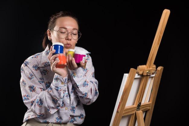 La donna tiene pennello e vernici su sfondo nero