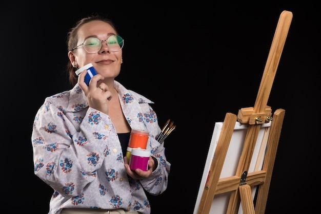 La donna tiene il pennello e le vernici su sfondo nero
