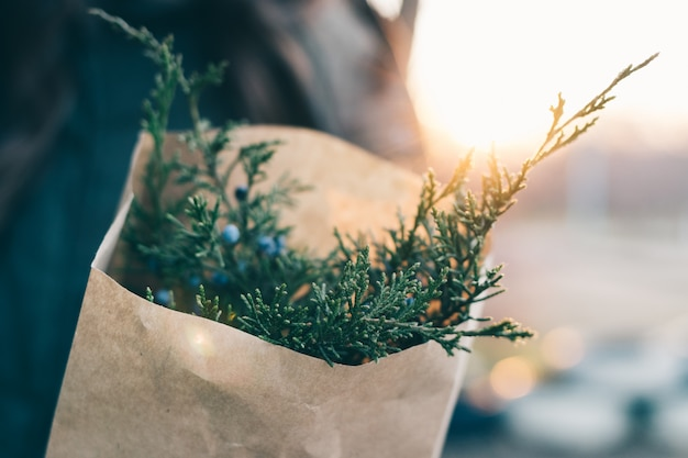 Woman holds a bundle of fir branches