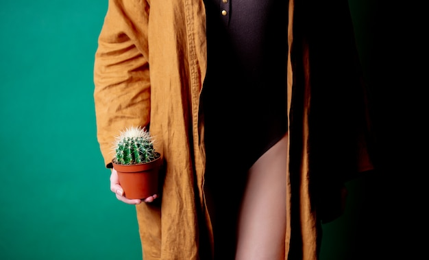 Woman holds cactus in her hands at foot level