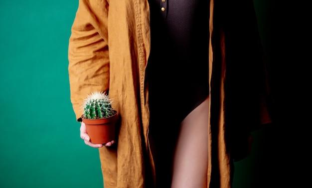 女性は足のレベルで彼女の手でサボテンを保持します