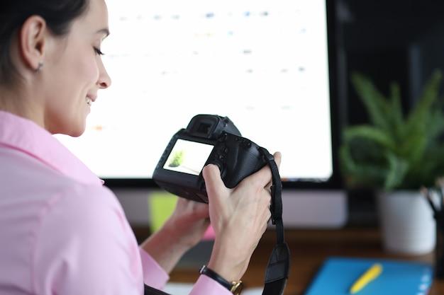 Женщина держит камеру и нажимает кнопки на концепции профессии фотографа на рабочем месте