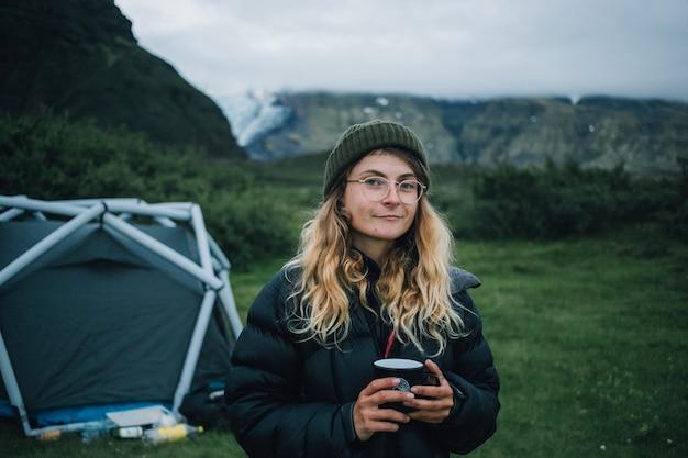 La donna tiene la tazza da campeggio durante un'escursione in islanda