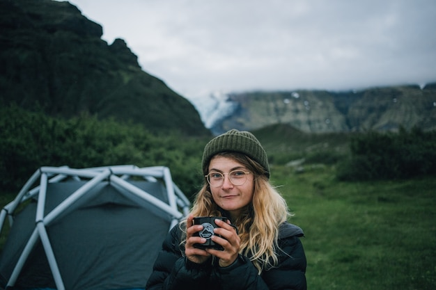 Woman holds camping mug on hike trip in iceland