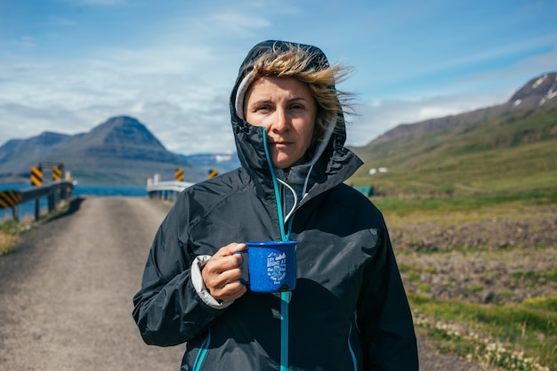 女性はアイスランドのハイキング旅行でキャンプマグを保持します