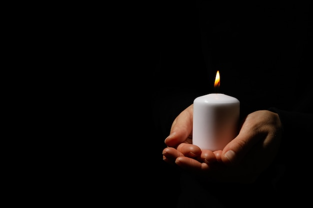 Woman holds candle on black