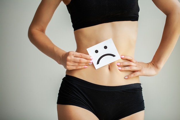 Woman holds a card of a sad smile near the belly