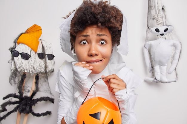 Woman holds carved pumpkin afraids of spooky creatures around bites lips dresses up in ghost cotume isolated on white