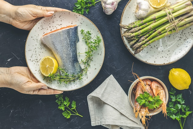 Woman holds ceramic plate with raw trout fish, thyme and lemon in hands on black concrete table surface surrounded plates with fresh raw asparagus, shrimp, prawn, parsley. healthy seafood background