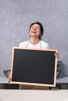 女性は手にチョークボードを持って笑います。スペースをコピーして、モックアップします。垂直フレーム。