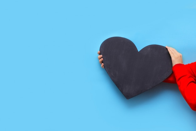 Woman holds a chalk board in the shape of a heart on a blue background for valentine's day