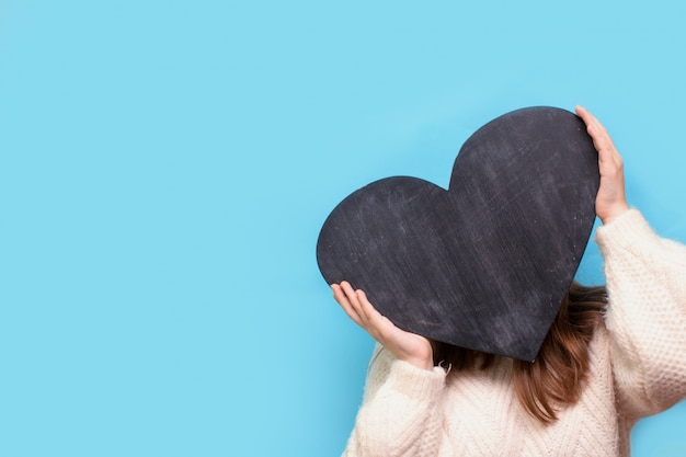 Woman holds a chalk board in the shape of a heart for valentine's day