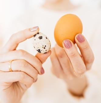 女性は手に鶏とウズラの卵を持っています。食品中のタンパク質、健康食品の概念、ビタミン、栄養素
