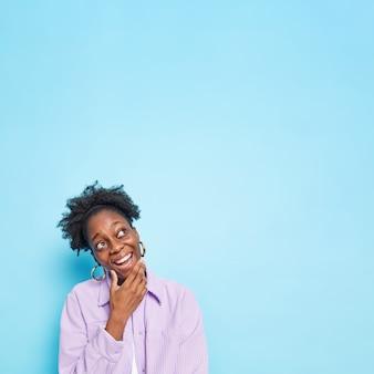 밝은 표정으로 턱을 잡고 있는 여성은 계획을 염두에 두고 파란색에 보라색 셔츠 포즈를 취하는 것이 행복하다고 느낀다