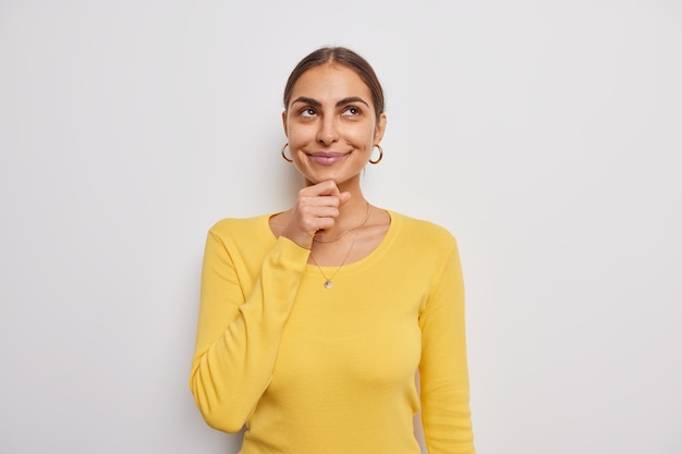 Woman holds chin focused above thinks about something smiles gently wears casual yellow jumper on white makes decision considers nice offer daydreams