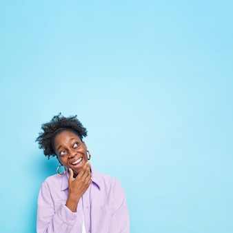 La donna tiene il mento focalizzato sopra con un'espressione allegra fa piani in mente si sente felice indossa la camicia viola posa sul blu