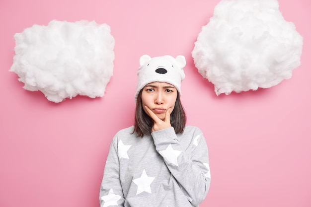 Woman holds chin and looks offended feels angry awakes in bad mood dressed in slumber suit soft hat with bear ears isolated on pink