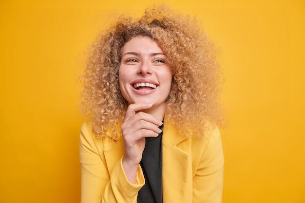 女性はあごの笑顔を心地よく感じ、フォーマルな服を着た幸せな表情で目をそらします。