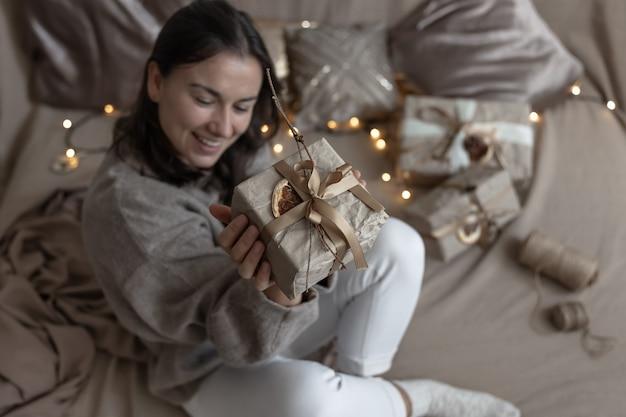 Una donna tiene in mano una scatola regalo di natale decorata in stile artigianale, decorata con fiori secchi e un'arancia secca, avvolta in carta artigianale.