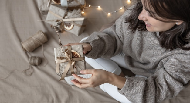 A woman holds a christmas gift box decorated in craft style, decorated with dried flowers and a dry orange, wrapped in craft paper.