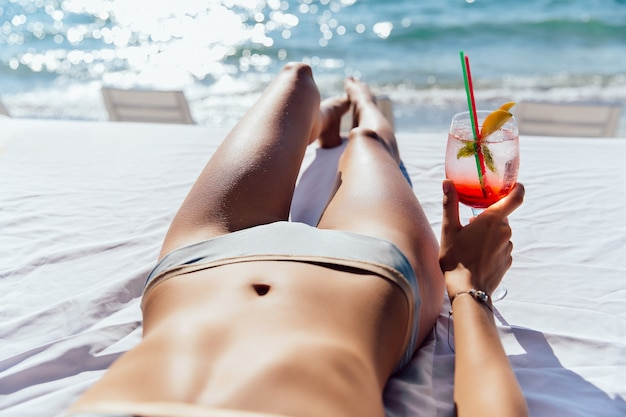 Woman holds a cocktail, while taking a sunbathe on sunbed, on the beach, near the sea.