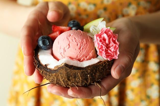 Женщина держит кокос с фруктовым мороженым, крупным планом