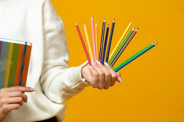 カラフルな鉛筆とメモ帳を保持する女性