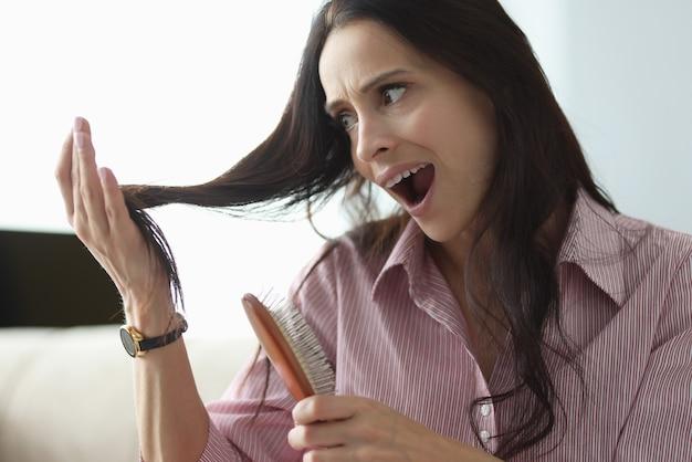 Женщина держит в руке расческу и в панике смотрит на свои волосы.