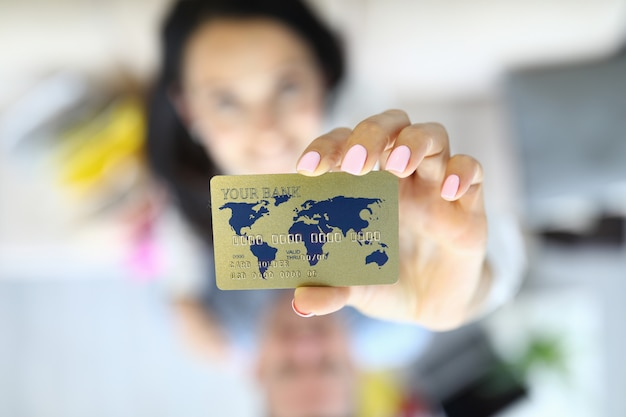 Woman holds credit card in her hands closeup.