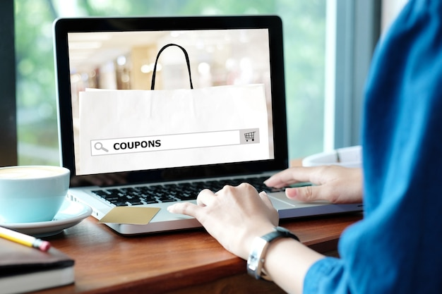 Woman holds credit card while uses laptop computer with shopping on line mock up.