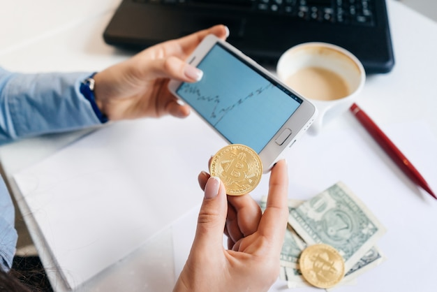 A woman holds a crypto-currency on the background of graphs