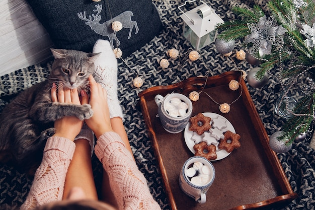 Woman holds a cup of chocolate under the christmas tree while playing with her cat