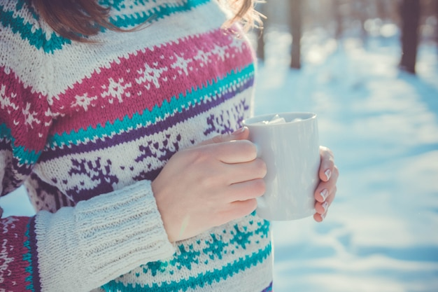 Woman holds cup of coffee with marshmallow in winter forest