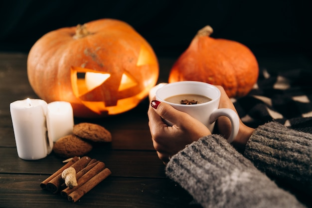 Woman holds a cup of hot chocolate in her arms before a halloween pumpkin