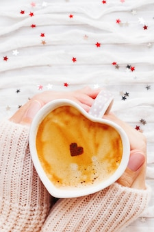Woman holds a cup of hot coffee with cinnamon heart.