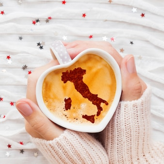 Woman holds a cup of hot coffee with cinnamon silhouette of italy.