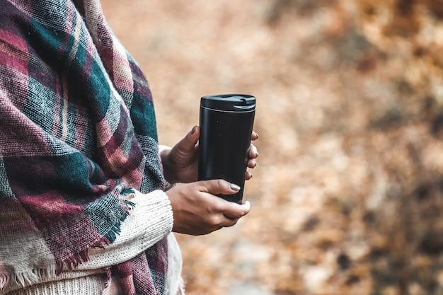 女性は森でカップを保持します