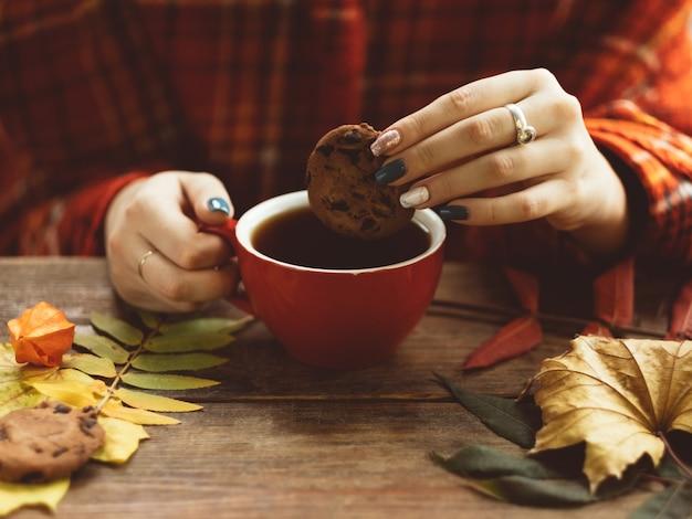 女性は秋の壁に暖かいお茶とクッキーを持っています。秋の喜び。病気の予防