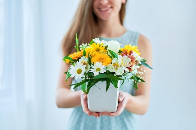 Весной женщина держит декоративную красочную яркую свежую цветочную шляпную коробку