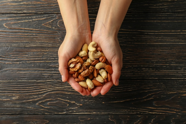 Женщина держит разные орехи на деревянных фоне. здоровое питание