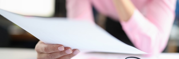 Woman holds documents over work table fixed consulting services for business concept