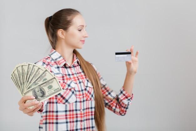 여자는 달러 지폐와 플라스틱 카드를 보유