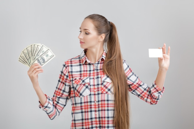 Woman holds dollar bills and plastic card