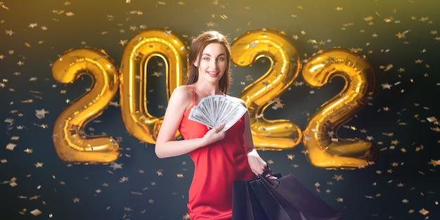 女性はドルを保持し、新年の買い物ブラックフライデーの風船の販売を祝う
