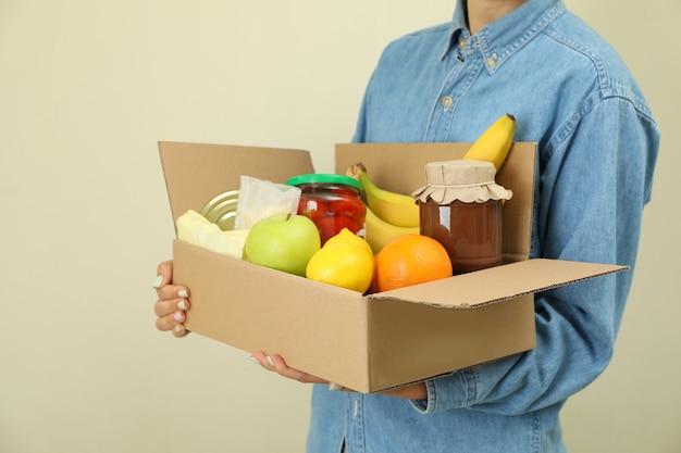 Женщина держит ящик для пожертвований на бежевом фоне
