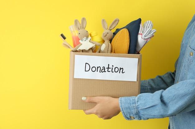 Женщина держит ящик для пожертвований на желтом фоне