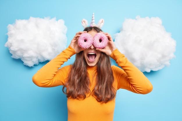 ゴーグルが甘いデザートを楽しんでいるかのように、女性は目にドーナツを持っている