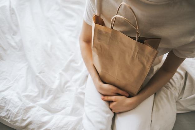 女性は手にエコショッピングバッグを持っています