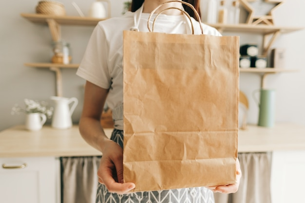 Woman holds eco shopping paper bag with food and vegetables in hands in kitchen delivery food take away