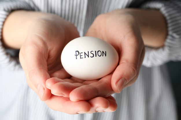 Woman holds egg with inscription pension, close up